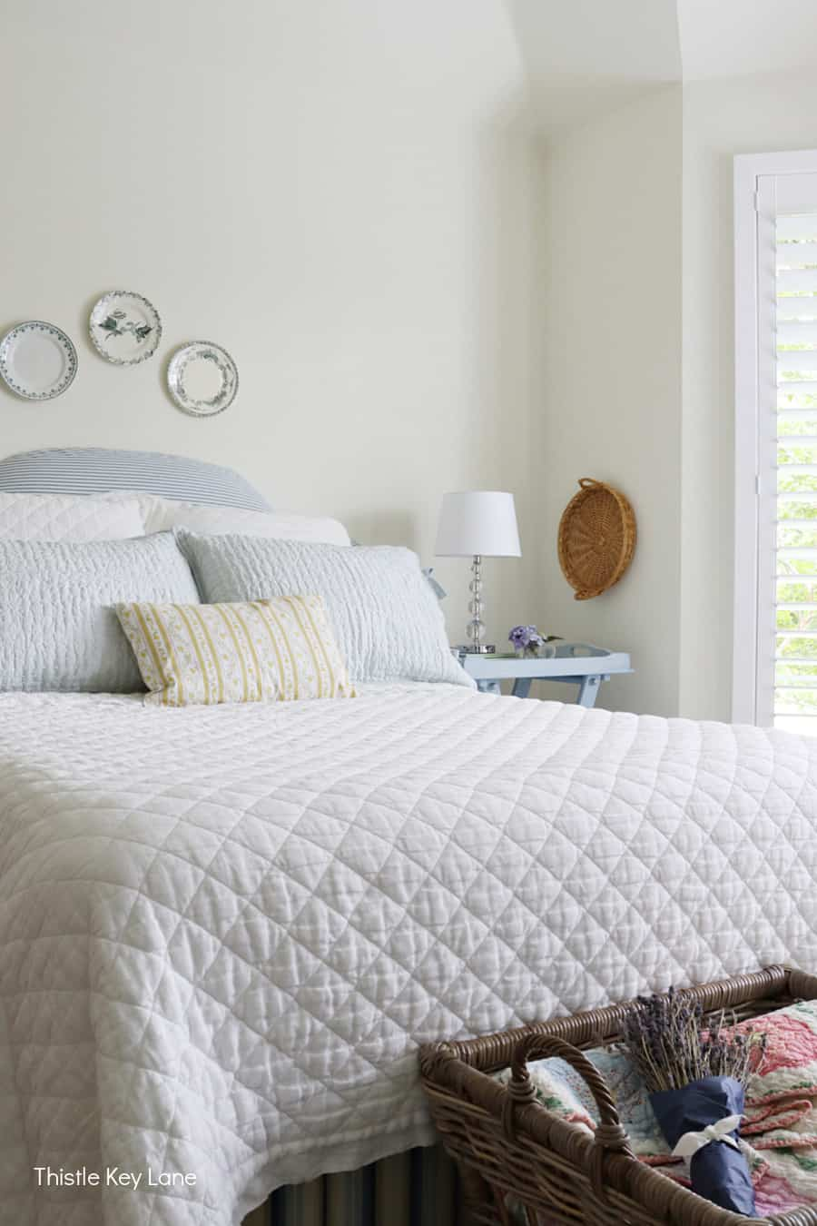 Bedroom with blue and white linens and plates over the headboard. Summer Bedroom Updates And A Quilt Basket.