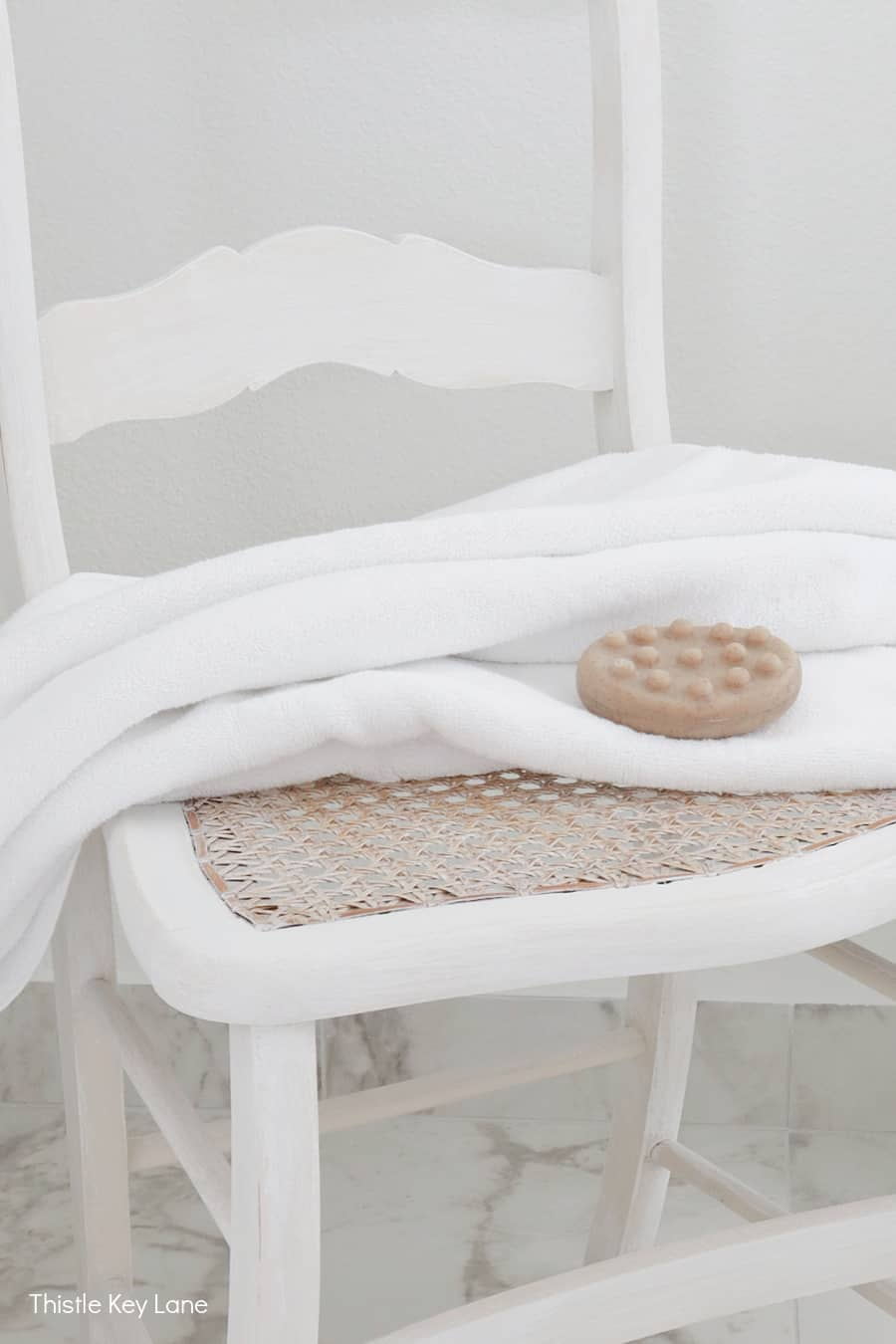 Cane chair with white towel and soap.
