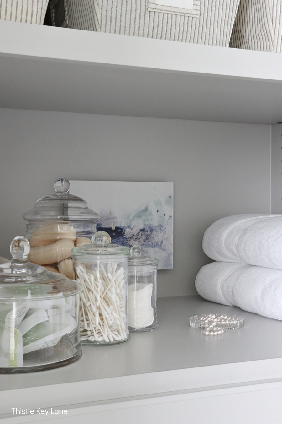 Glass storage jars and abstract artwork. Organizing A Master Bathroom Linen Closet.