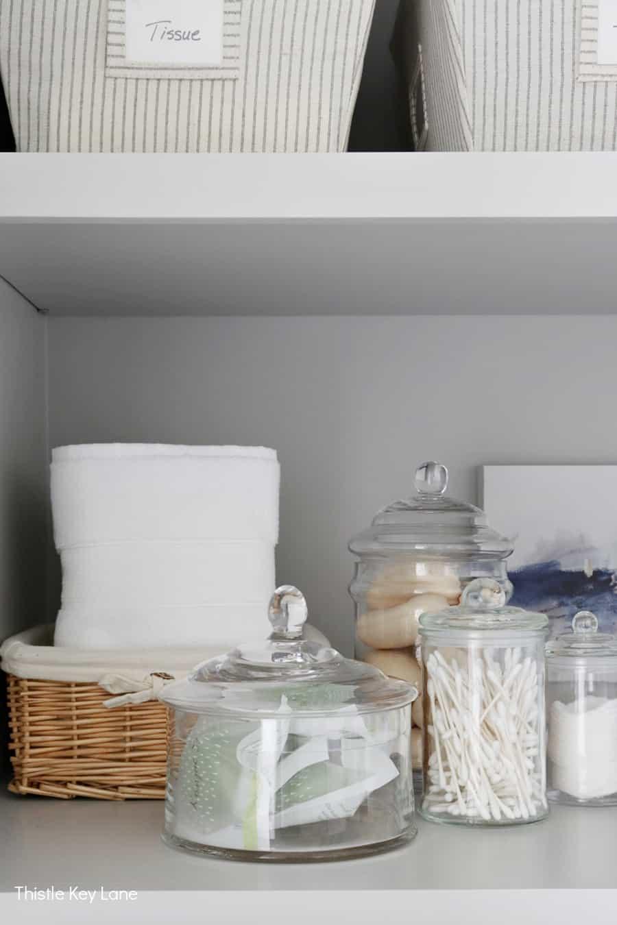 Glass storage jars on linen closet shelf. Organizing A Master Bathroom Linen Closet.