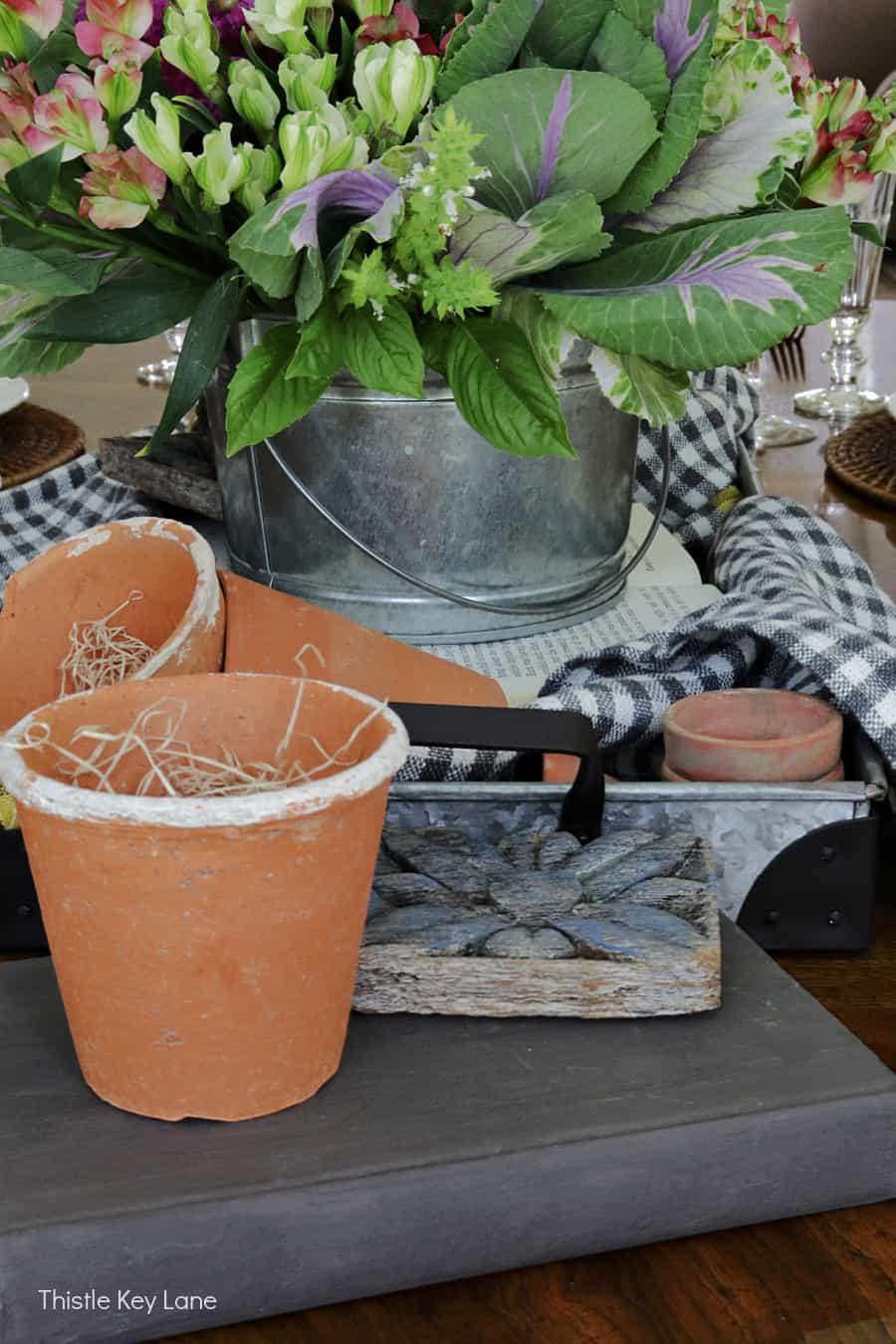 Adding wood architectural pieces for texture. Kale Flower Arrangement And Garden Tablescape.