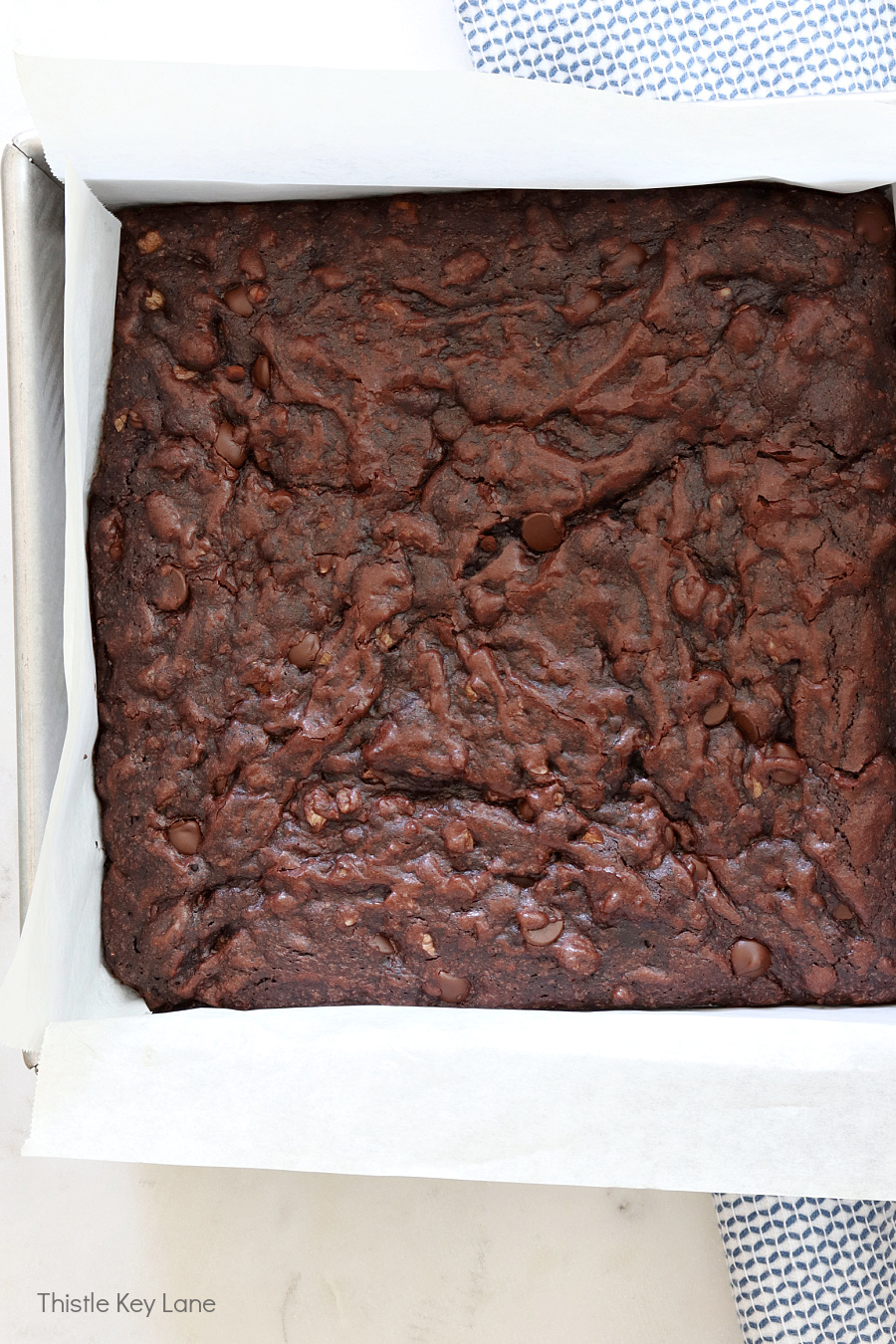 Parchment lined pan holding brownies. Dark Chocolate Fudge Brownie Recipe.