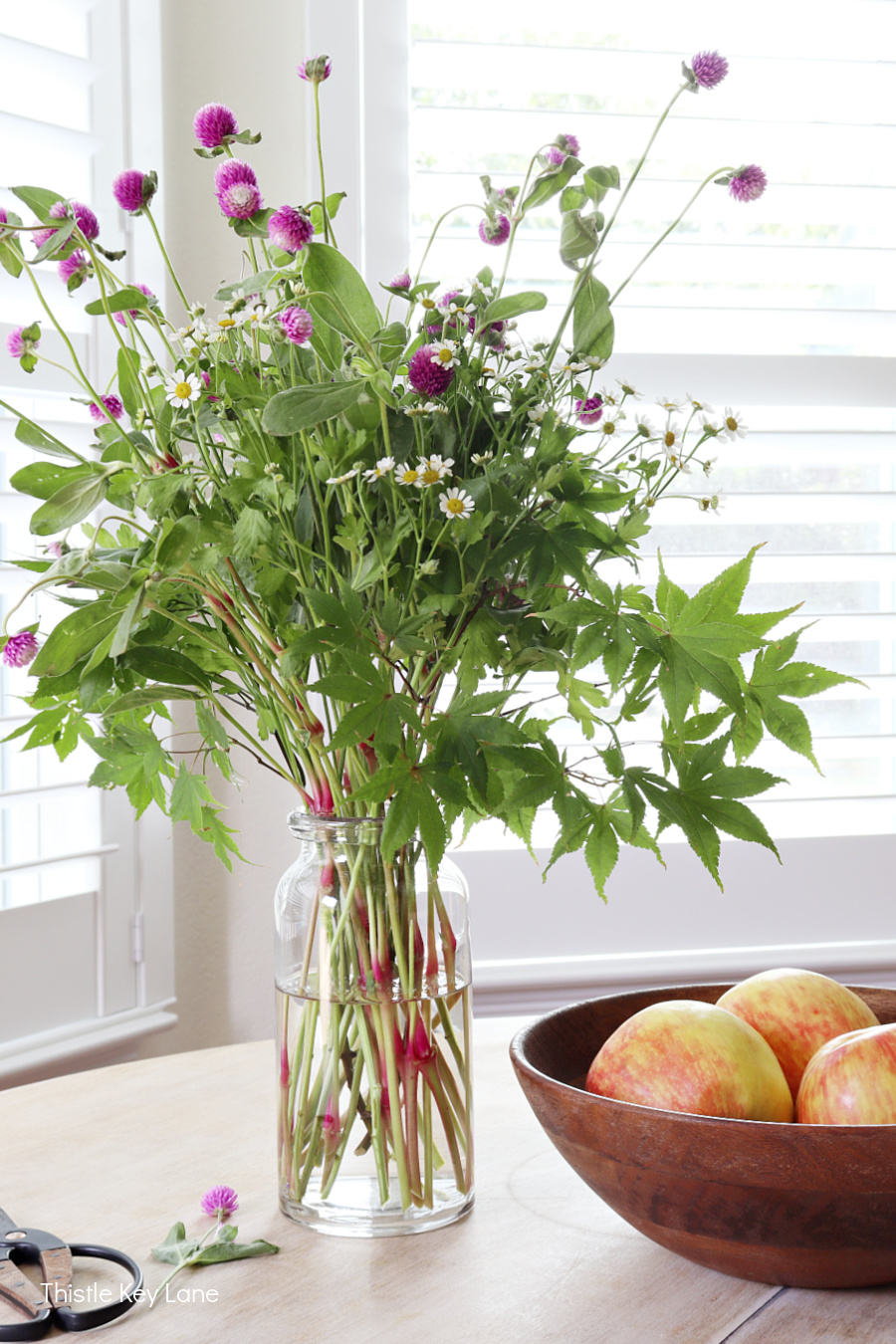 Bachelor button and camomile flower arrangement with a bowl of apples.