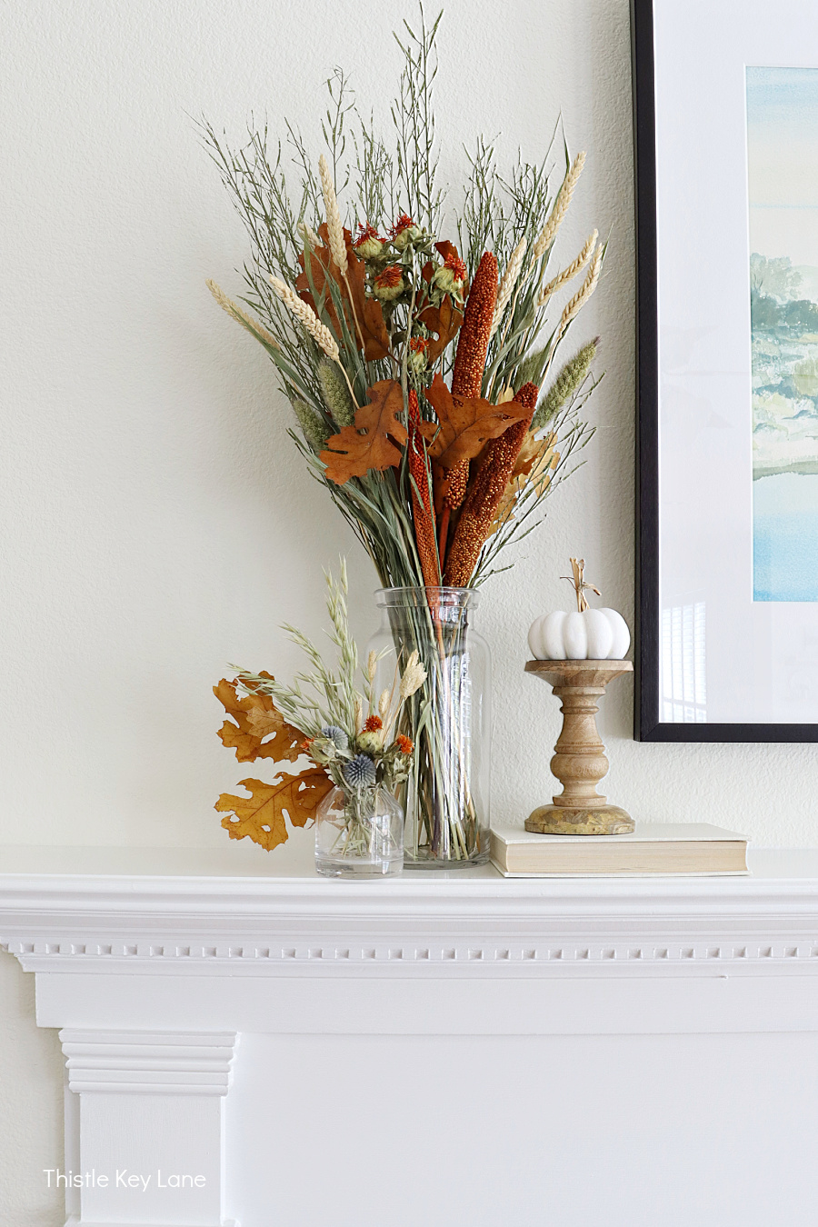 Dried leaves, flowers and grasses in a glass vase. Decorating A Fall Mantel With Dried Arrangements.
