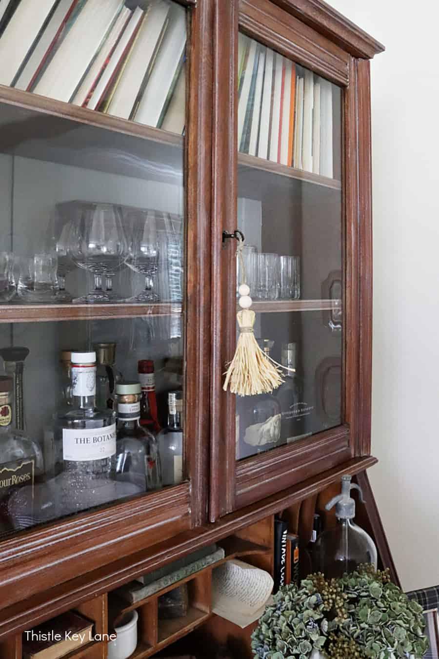 Raffia tassel tied to a key hanging from a cabinet. How To Make Raffia Tassels.