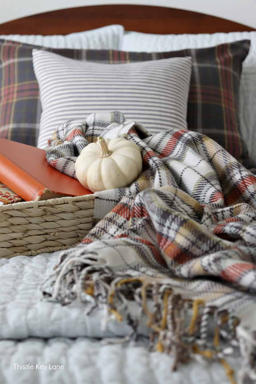 Woven tray with white pumpkin, books and plaid throw. Simple Fall Bedroom Ideas.