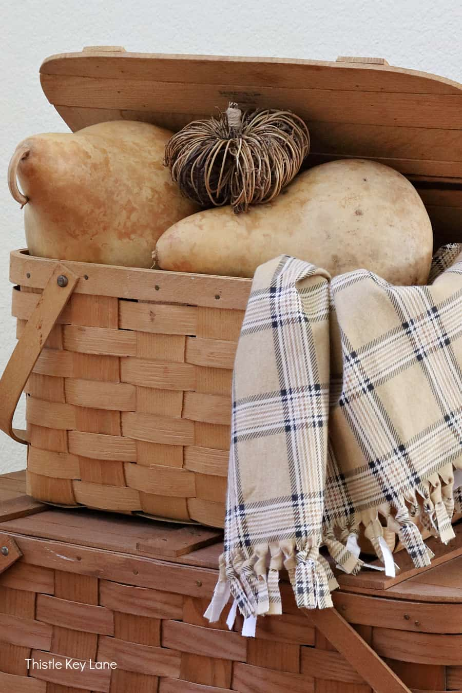 Fall gourds and a twig pumpkin in a picnic basket. Simple Fall Porch And Entryway Ideas.