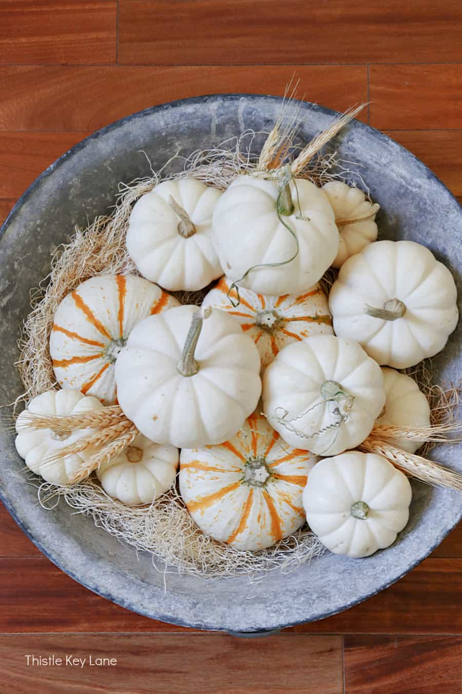 Yellow tiger stripe and white pumpkins in a zinc bowl. Simple Fall Porch And Entryway Ideas.