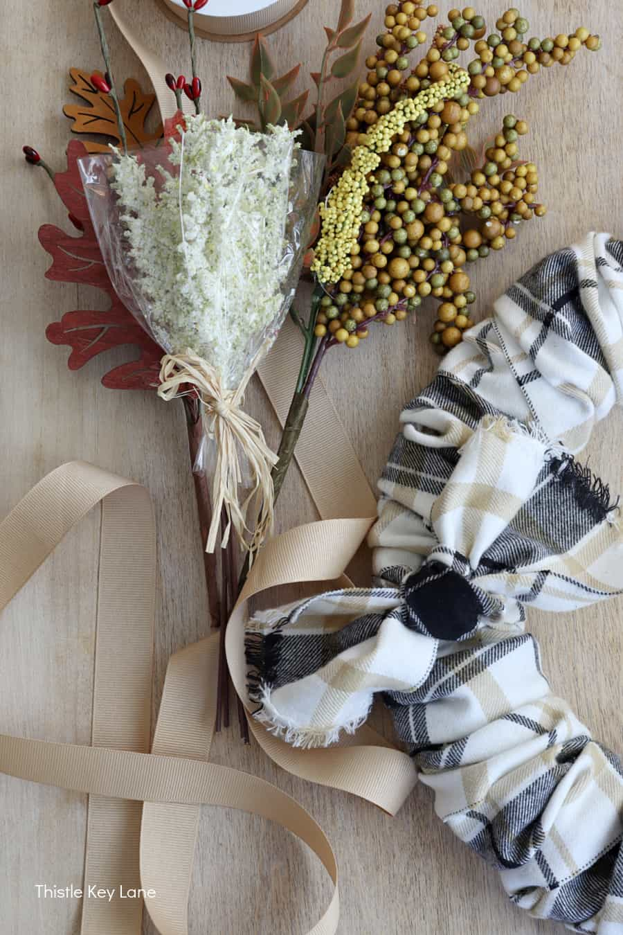 Floral picks in fall colors next to plaid wreath.