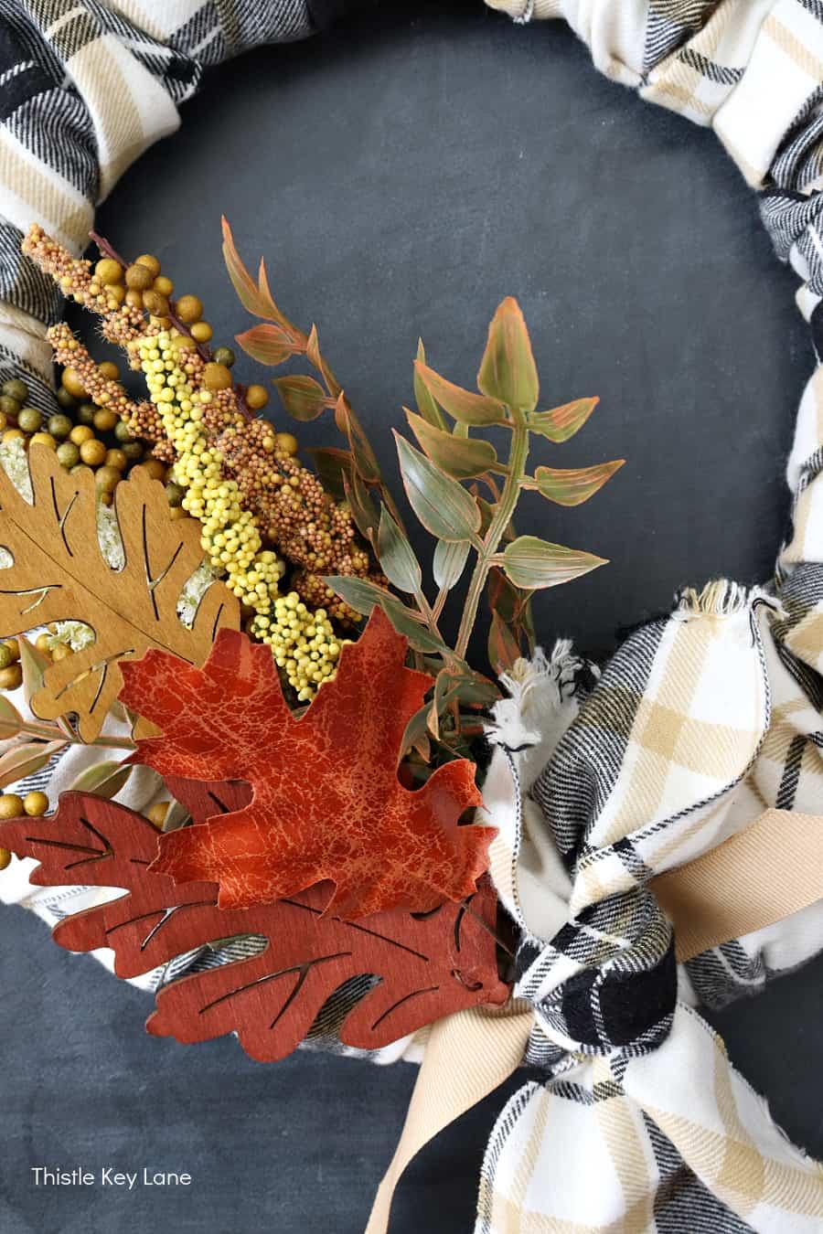 Fall foliage on a black and white plaid flannel wreath. DIY Plaid Fall Wreath With Autumn Colors.