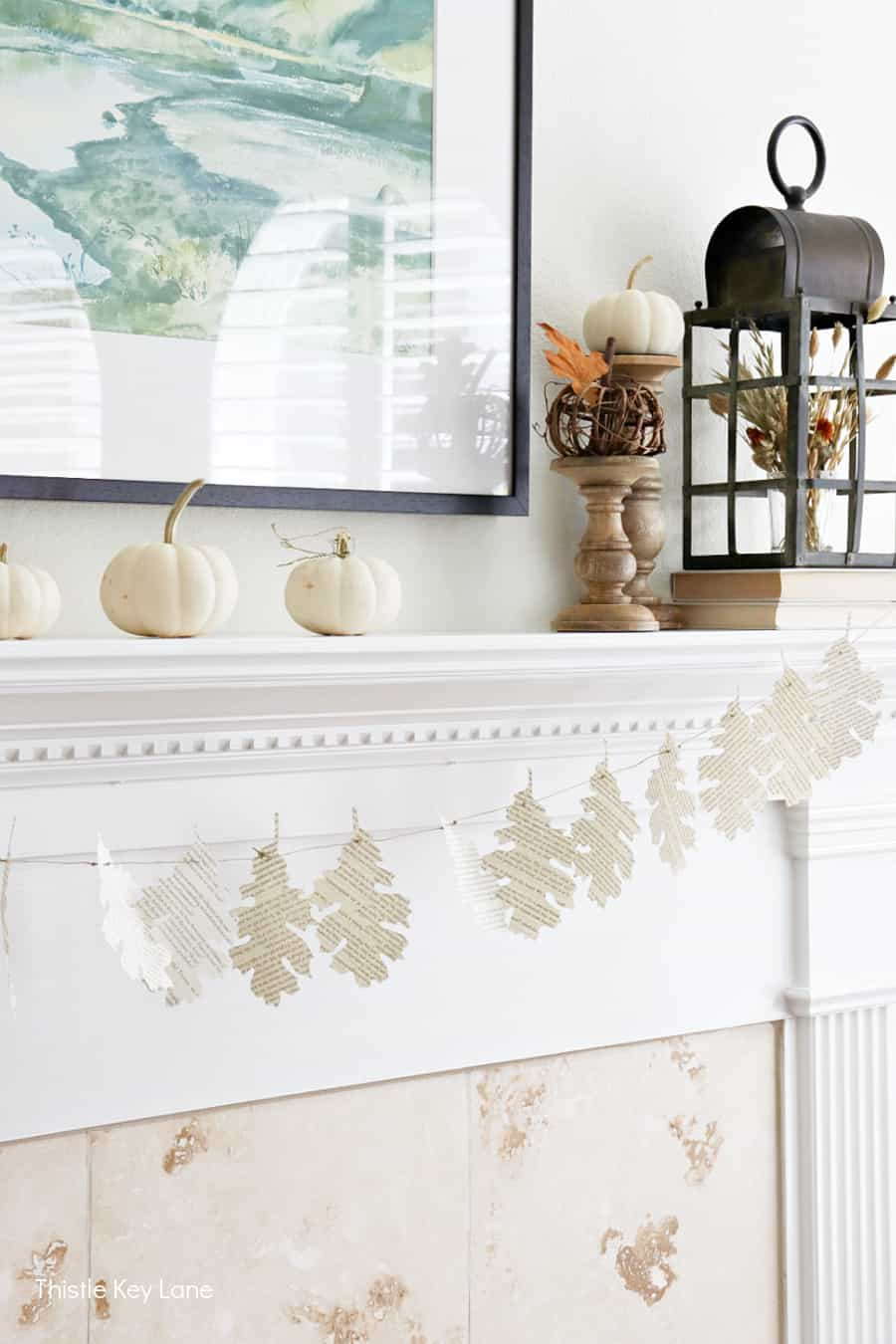 Leaf garland and white pumpkins on a mantel.