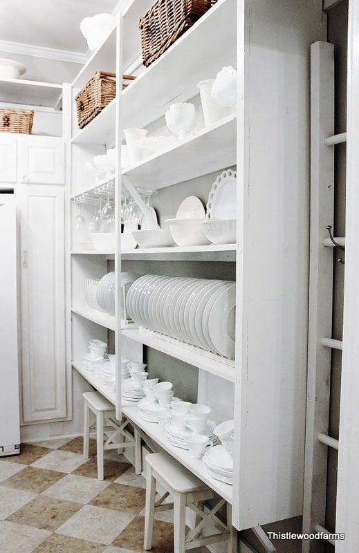 Shelves full of white dishes and linen lined baskets are perfect for the pantry
