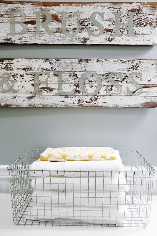 Rustic wooden signs and wire bins for towels add farmhouse flare to any bathroom.