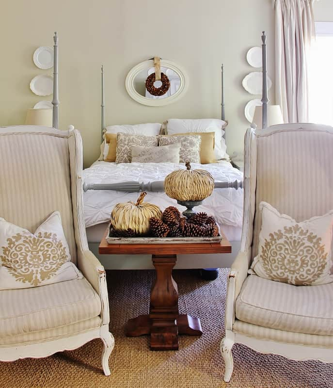 A master bedroom scene; in between two vintage reading chairs is a dark stained wooden coffee table with a wooden tray filled with decorative pumpkins and pinecones