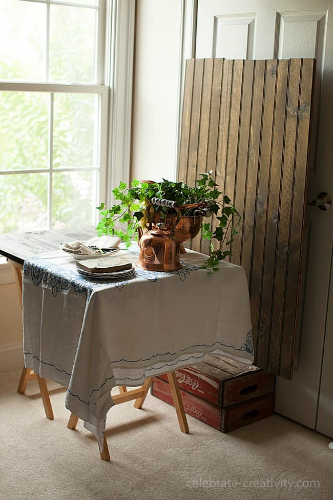 This large window lets in a lot of natural light that brightens up the table scene with a copper potted plant