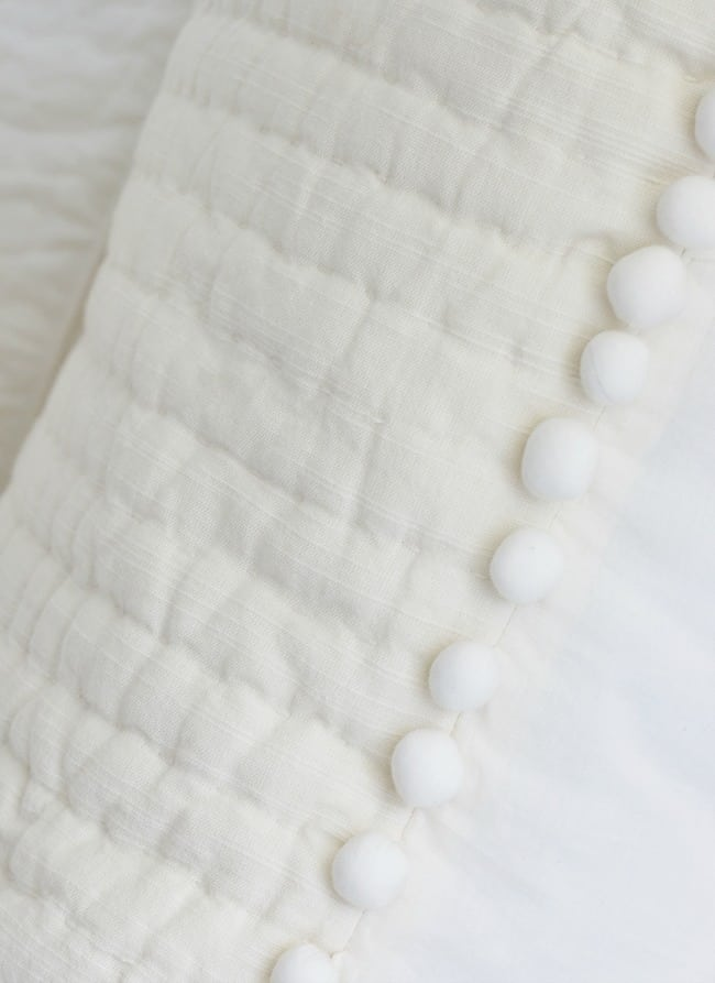 Soft white bed linens on a farmhouse style bed