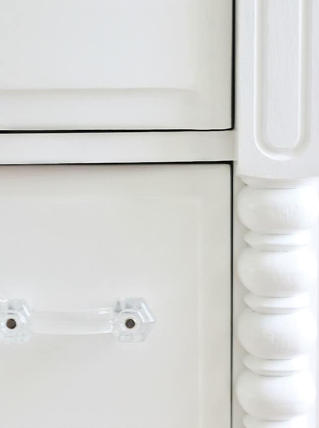 Close up wood working details on a white painted dressed with decorative drawer handles