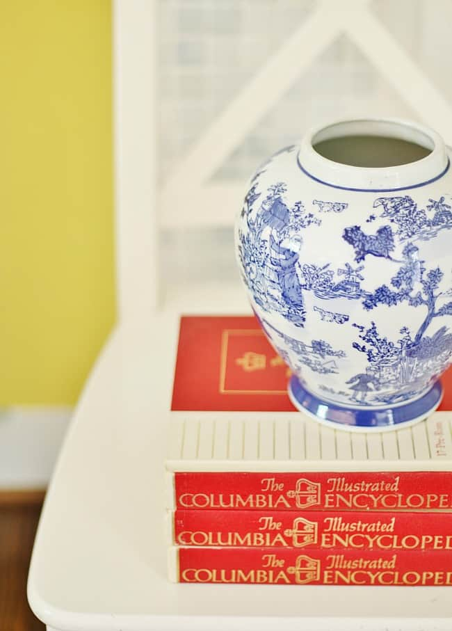 Gorgeous detailed vase sitting atop a stack of encyclopedias, and yellow painted wall in the background