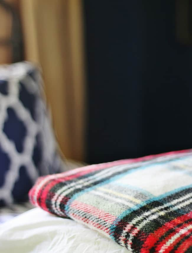 A close up of the plaid blanket on the bed