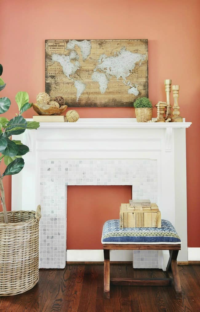 White wood mantle in front of a rusty red-orange wood wall. The mantle is decorated with candle sticks and vintage wooden spheres. A map of the world hangs on the wall