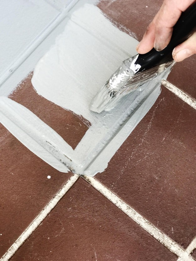 using brick paint on the porch with paint brush