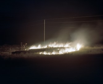 A fire breaks out during Fourth of July celebrations near the home of Jill Plumage, at the Fort Belknap Agency. Neighbours come running to help subdue the fire, caused by a home fireworks display gone awry, with shovels and spades while they wait for the Tribe's fire department to arrive. In northern Montana, where the reservation is located, by mid summer the earth is scorched and the grasses are dried, making the land highly flammable and susceptible to large fires.