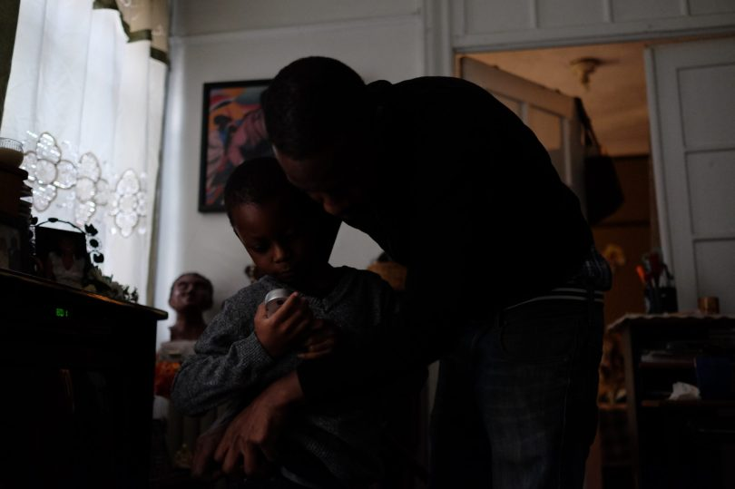 Bronx, NY Oct. 12, 2014 Travis helps Zaire get on his sweater and jeans. Photo by M.B. Elian