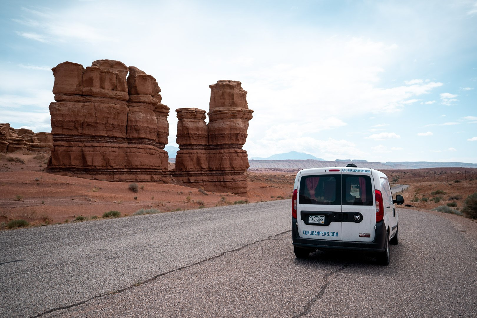 A camper van parked on the road with a large rock formation in Capitol Reef, Utah