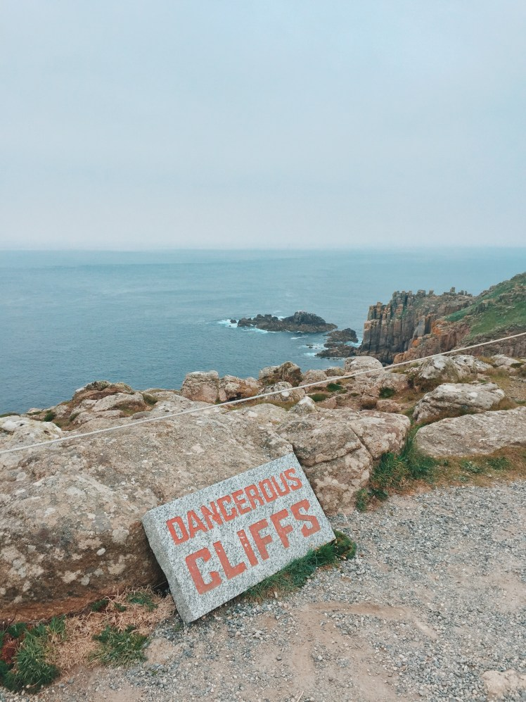 The Dangerous Cliffs sign with safety rope marking out the correct place to stand to enjoy the view at Land's End. The background shows the dangerous rocks and wild waters below.