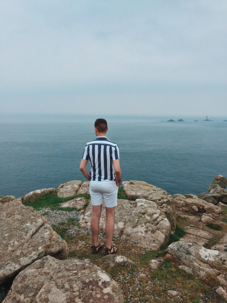 Tommy overlooking at the the little islands where Longships Lighthouse keeps the ships from crashing. The ocean is vast and blue and compliments my outfit of white and blue.
