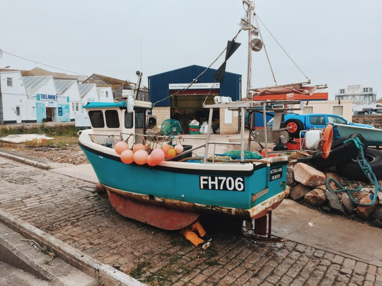 A fisherman repairing his docked blue fishing boat on land in Newlyn harbour