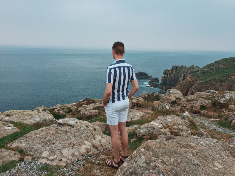 Tommy in his nautical outfit overlooking the beautiful and vast views where the sea and sky meet in a variety of blues. The details for the outfit include a white and blue stripy short sleeved shirt, short white shorts and brown gladiator sandals.