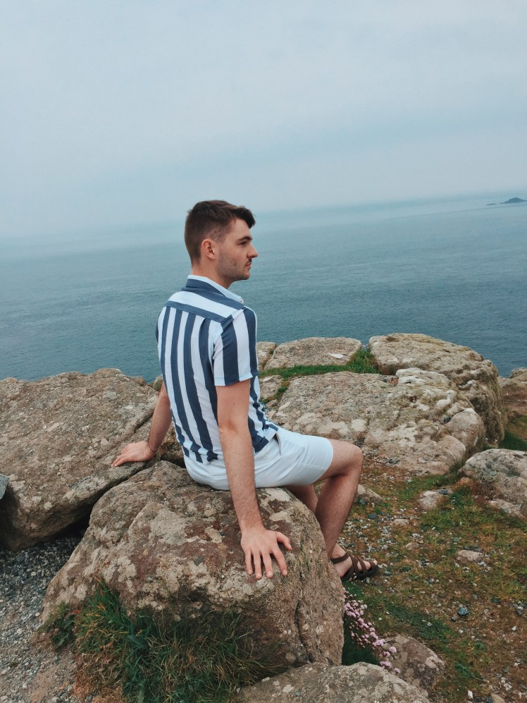 Tommy perched on a rock looking a little nervous with the view of the Atlantic and Celtic ocean behind him.