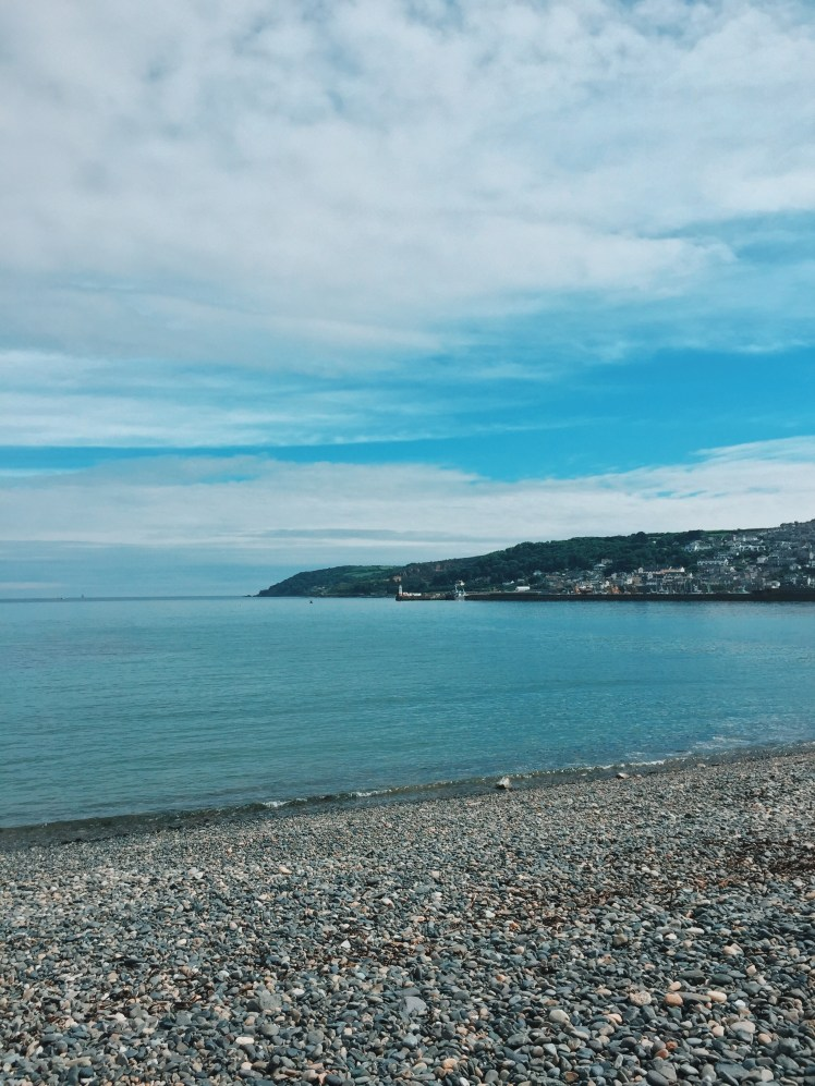 Penzance pebble and sand beach with views of the Newlyn, its harbour and lighthouse