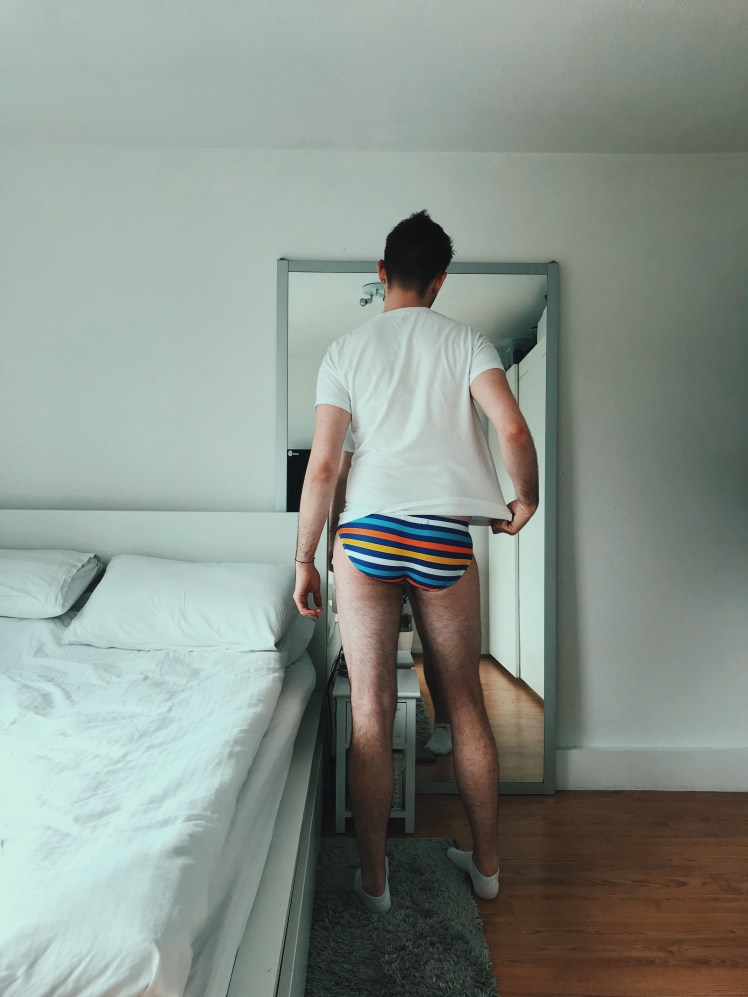 The back view of the 'Brian' swim trunks showing the, no cheek peek feature and fit on the bum. The colour is the stripes option which is a mixture of dark blue, light blue, yellow, orange and white.