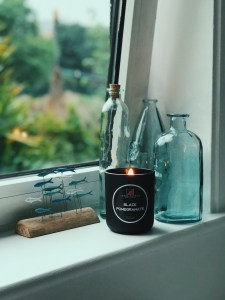 Black Pomegranate by James Patrick lit on the windowsill, setting the mood perfectly against my glass bottles and fish sculpture