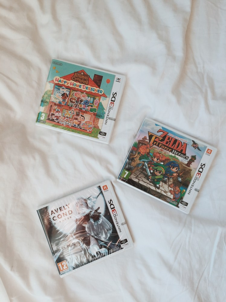 A flatlay of the 3 games that were included with my 3DS bundle: Animal Crossing Happy Home Designer, Zelda TriForce Heroes and Bravely Second