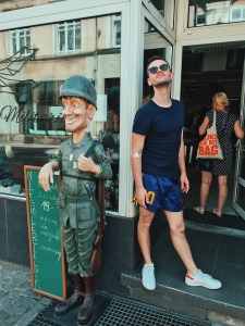 Jacob posing next to a quirky statue outside a Polish charity shop