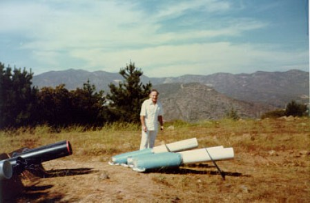 """HATFIELD FLAT, CALIFORNIA, 1984 Long series of experiments to engineer rain into Los Angeles in July, when region is statistically rainless, required ten years of avocational work. Operator here stands with """"bazooka"""" type devices, which coupled a Wilhelm Reich-type """"accumulator"""" into a projective resonant section (white). Hatfield Flat is about 14 miles east of San Diego and 1200 feet above sea level. Excellent results were obtained."""
