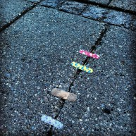 Fin gadekunst gør opmærksom på revnerne i fundamentet ved at sætte børneplaster på. Et fint stykke stof til refleksion.