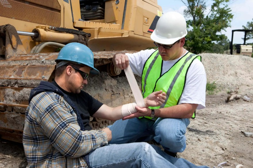 construction worker receiving first aid by another worker at a construction site