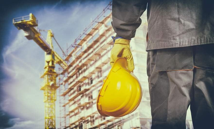construction worker in protective gear looking toward scaffolding at construction work site