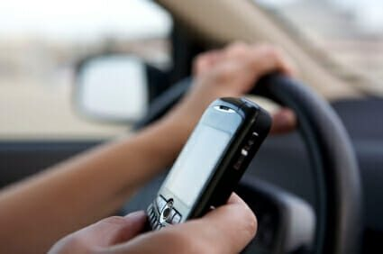 Person driving while using a handheld cell phone.