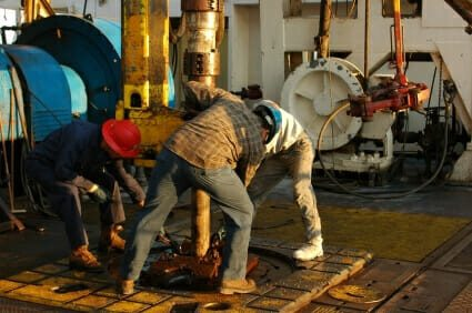 Oil workers operating oil drilling equipment