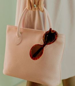 purse with sunglasses hanging over edge