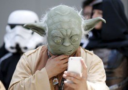 "A cosplayer dressed as ""Star Wars"" character Yoda looks at a mobile phone at a Star Wars Day fan event in Tokyo"