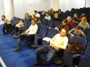 About 20 people in a lecture-theatre, there are more blue seats than people.