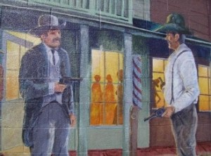 """A Dangerous Arrest"" by Richard Perkins, John Knowlton, Kathy Sexton, Jenna Morgenstein, MaryGipson-Knowlton, 2000. This mural shows an ""Old West"" event that broke the peace and quiet of  Bishop on March 10, 1887. Philip Staiger was reported to be drunk and disorderly, threatening a abystander with a gun and resisting arrest. 207 West Line Street, Bishop Police Station . 11.5' x 15'"