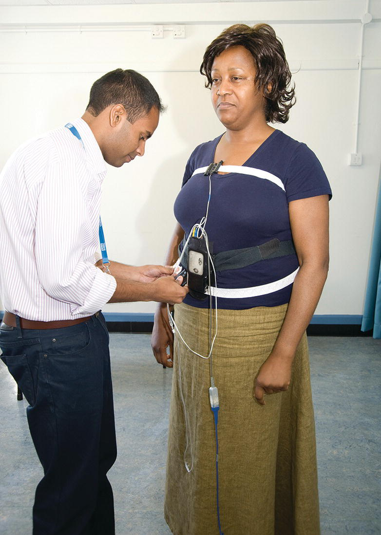 Photo displaying a woman being fitted with an oximeter around her body by a man in front of her.