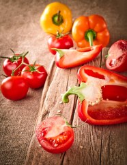 red-yellow-orange-peppers-tomato-wooden-surface